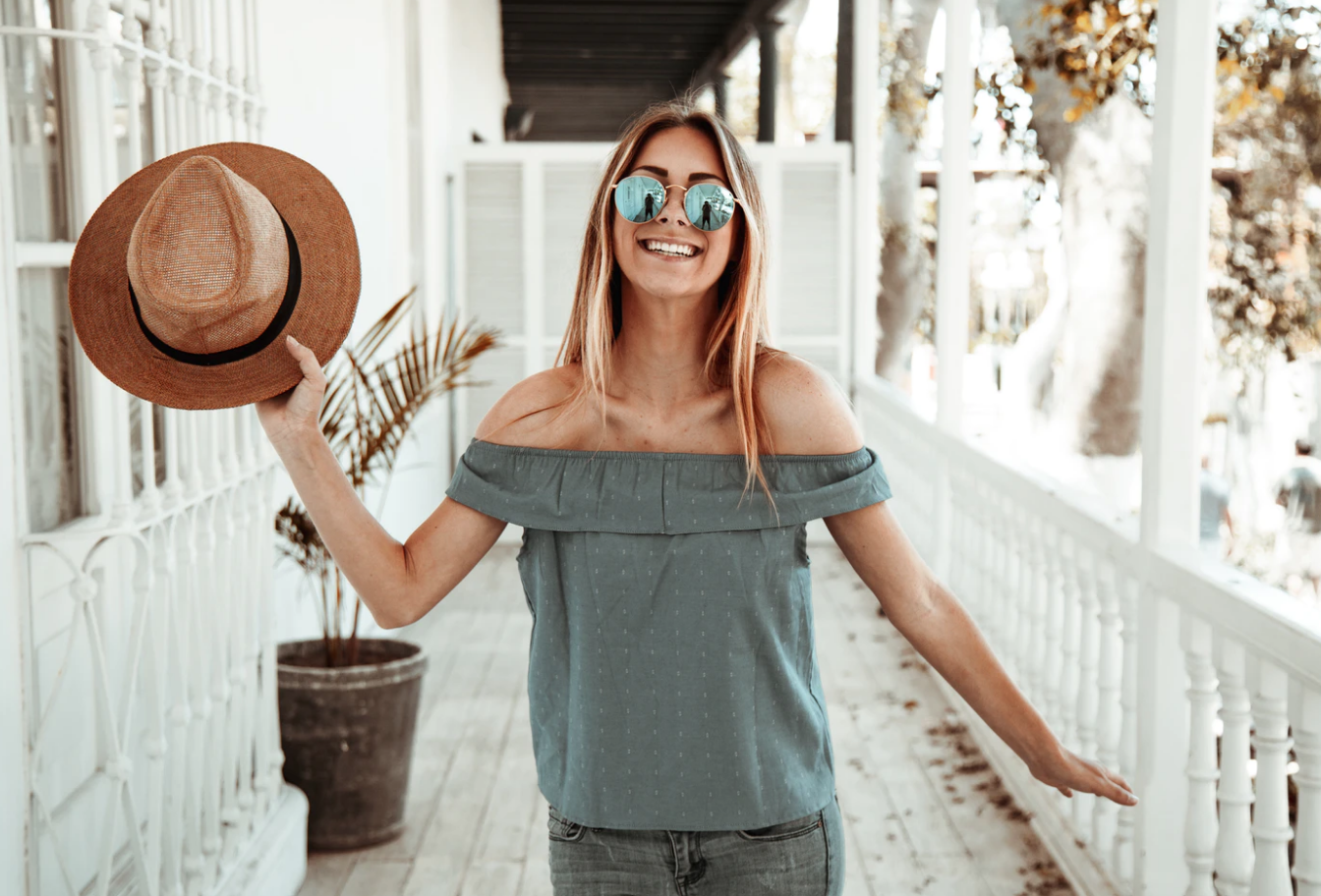 afford tuition costs, woman holding hat smiling