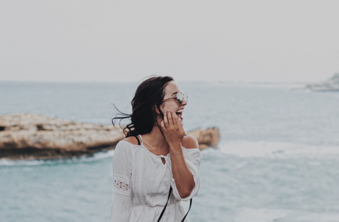 travel woman with sunglasses laughing on beach