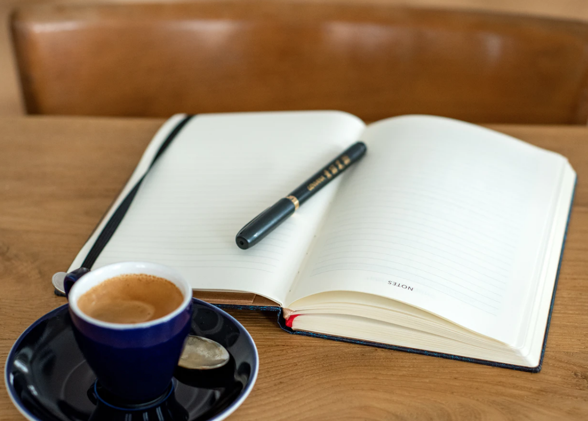 espresso and open notebook with a pen on a wooden table, mothers returning to school