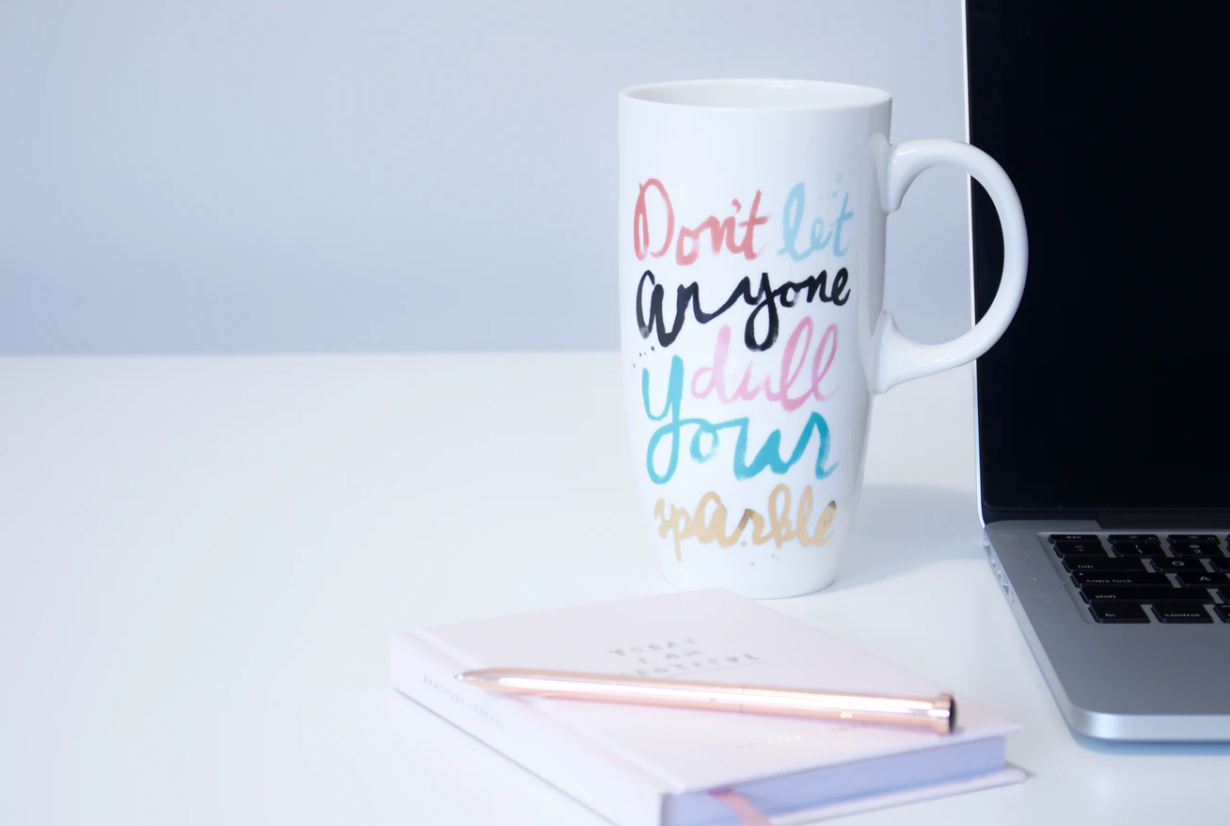 """tall coffee mug that reads """"don't let anyone dull your sparkle"""" placed beside notebook, pen, and open laptop, letters of recommendation"""