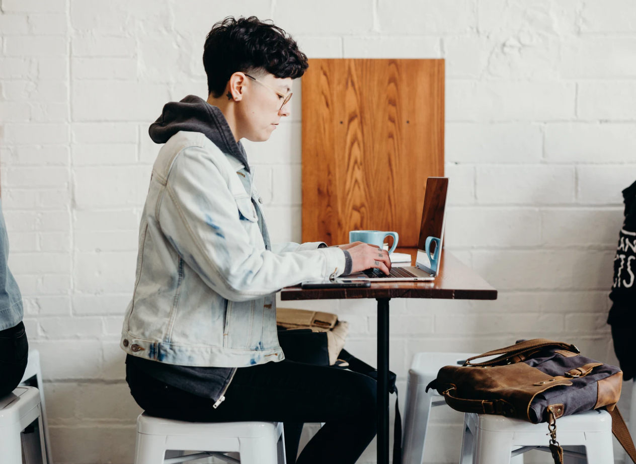 what is a scholarship , profile image of student in a jean jacket sitting in front of open laptop