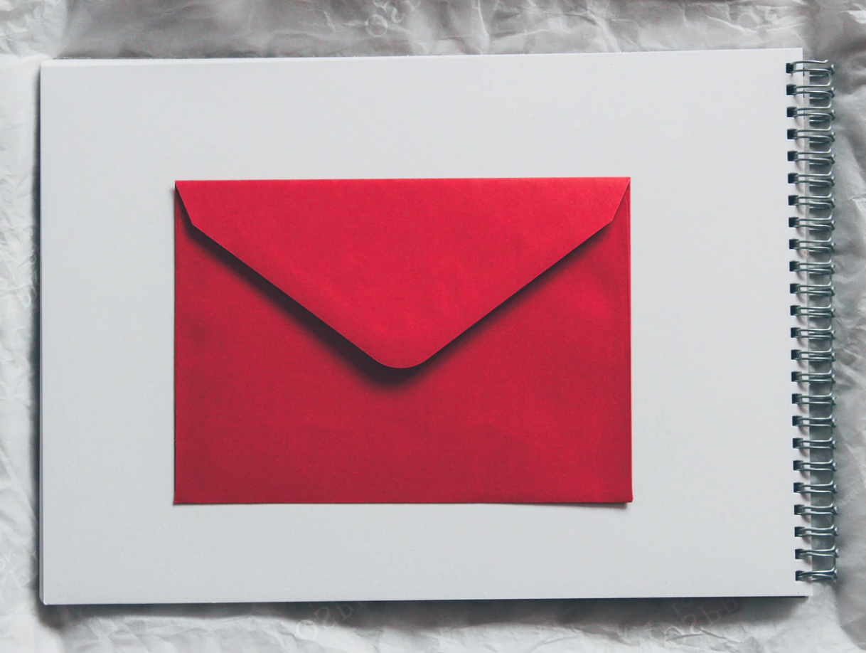 letter of recommendation red envelope lying flat on white sketchbook page